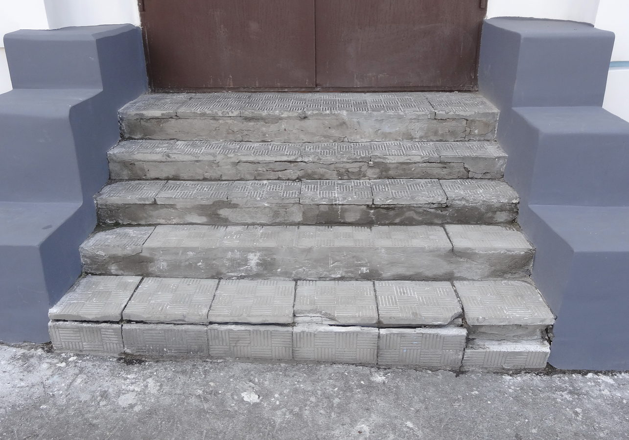 Old stone gray steps with wear marks of destruction with scratches and cracks. Entrance to the street in the shop in the old part of the city.