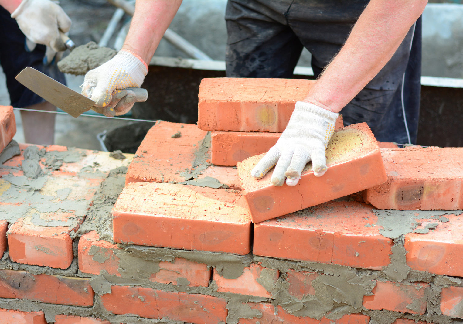 Bricklayer hands in masonry gloves and trowels bricklaying house wall. Building contractors bricklaying house wall,  masonry.