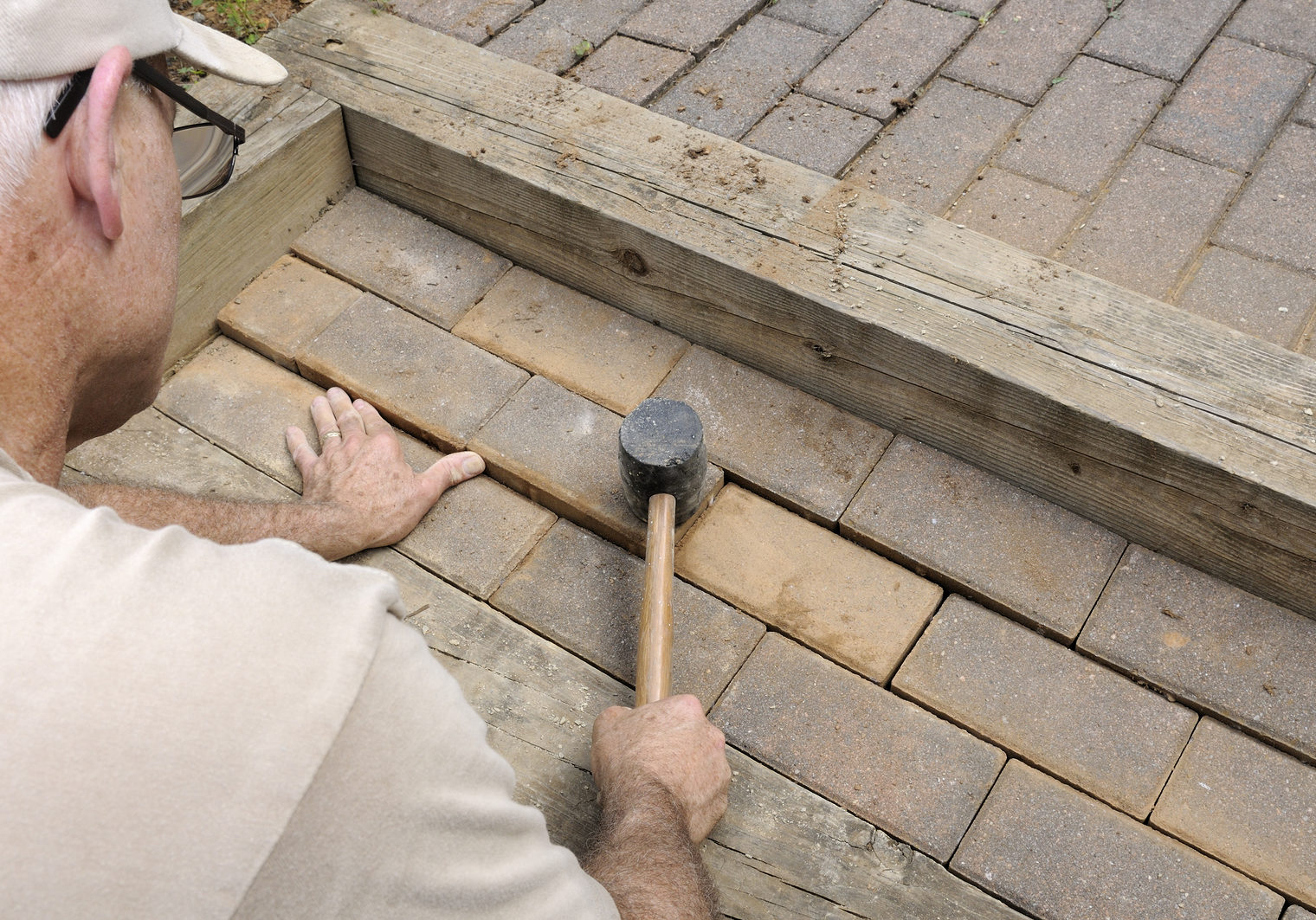 Construction worker installing brick pavers on walkway and steps.