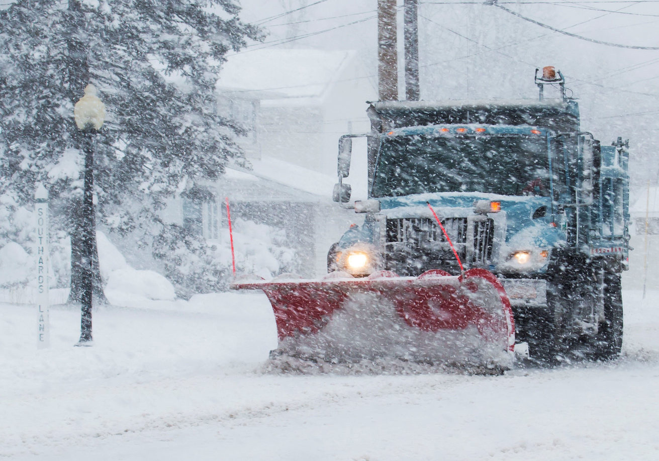Snow plow is plowing the roads during a storm